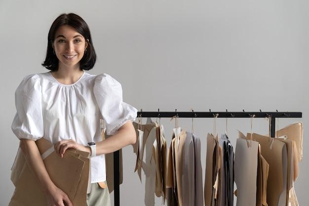 Felice giovane stilista di moda indossa una camicetta bianca alla moda che tiene i modelli vicino al gancio in studio