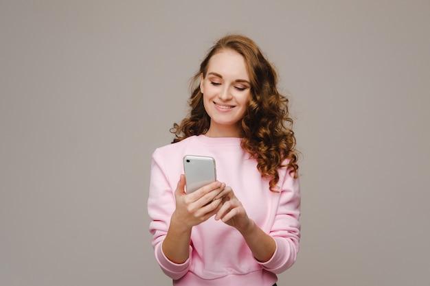 Una giovane ragazza felice che tiene un telefono lo esamina e sorride