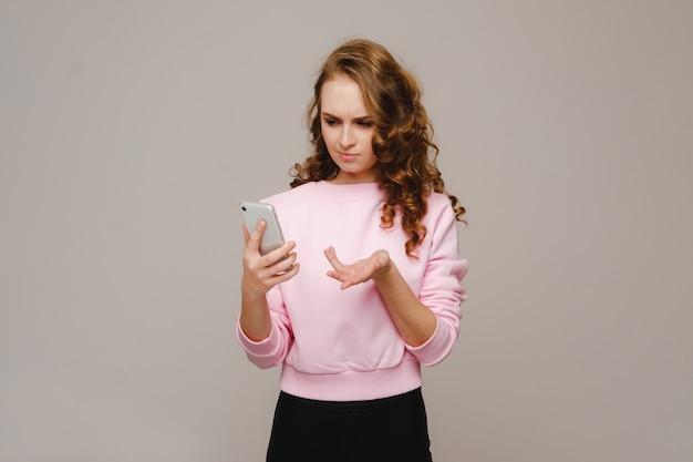 Una giovane ragazza felice che tiene un telefono lo esamina e sorride.