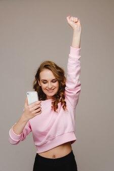 Una giovane ragazza felice tiene il telefono, guarda dentro e sorride alzando la mano.