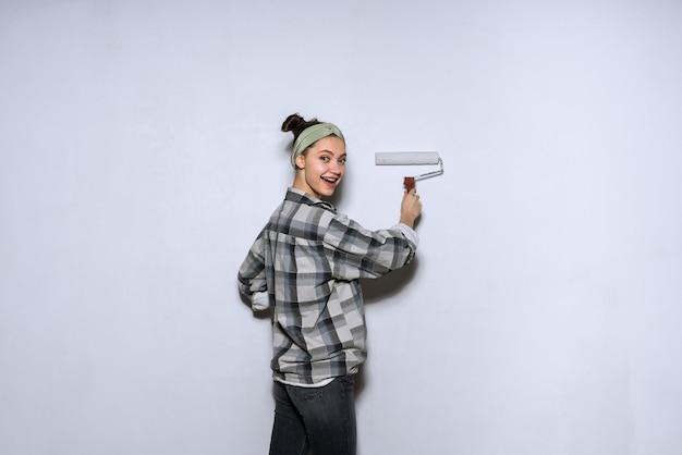 La ragazza felice in camicia a quadri colora il muro con un rullo di bianco