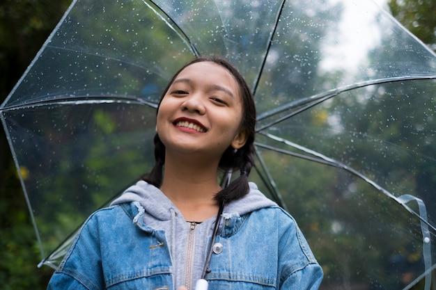 Ragazza felice che gioca con la pioggia nel giardino verde.