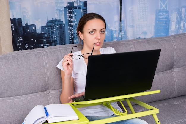 La ragazza felice mette gli occhiali alla bocca mentre lavora su un laptop facendo i suoi affari da casa seduta su un divano e sorridendo nel soggiorno in un'atmosfera rilassata