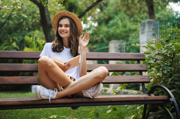 Ragazza felice che legge un libro mentre era seduto al parco all'aperto, agitando la mano
