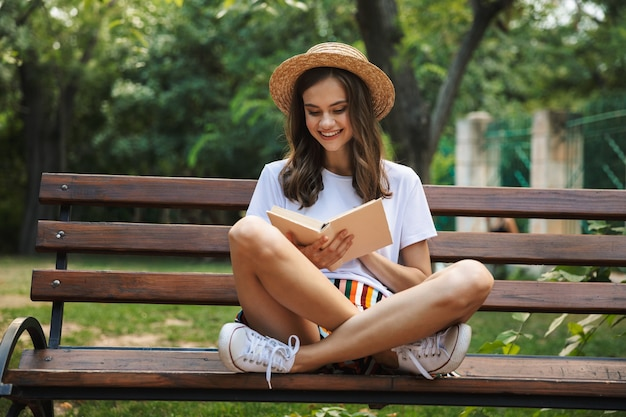 Ragazza felice che legge un libro mentre era seduto al parco all'aperto