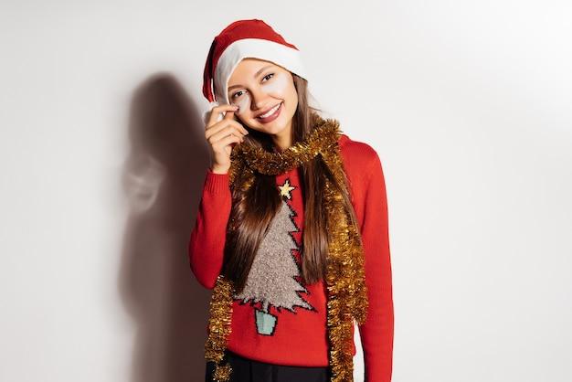 La ragazza felice in maglione rosso di natale celebra il natale, sotto i cerotti degli occhi