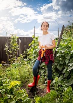 Ragazza felice in stivali di gomma rossi che lavora al giardino sul retro