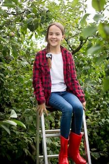 Ragazza felice in stivali di gomma rossi che si siede sulla scala a libro al giardino