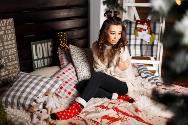 Giovane ragazza felice in maglione alla moda lavorato a maglia vintage con un sorriso sul letto alla vigilia di natale