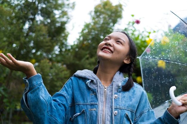 Felice giovane ragazza indossare giacca di jeans che gioca con la pioggia nel giardino verde.