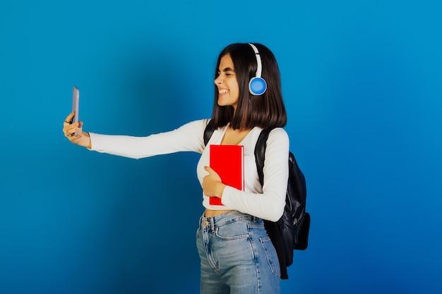Felice giovane ragazza con zaino nero, taccuino rosso e cuffie, sbattendo le palpebre mentre prende selfie.