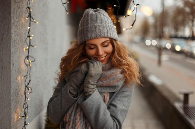 Ragazza felice con un sorriso magico in vestiti di maglieria moda in un cappello lavorato a maglia in posa in città vicino alle luci