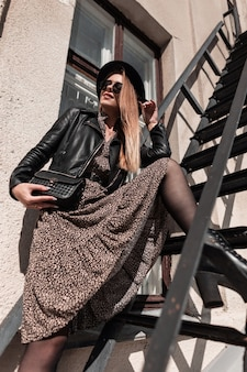 Ragazza felice con un sorriso in un cappello alla moda con una giacca di pelle e una gonna vintage con un'elegante borsa in posa vicino a un edificio su una scala in una giornata di sole