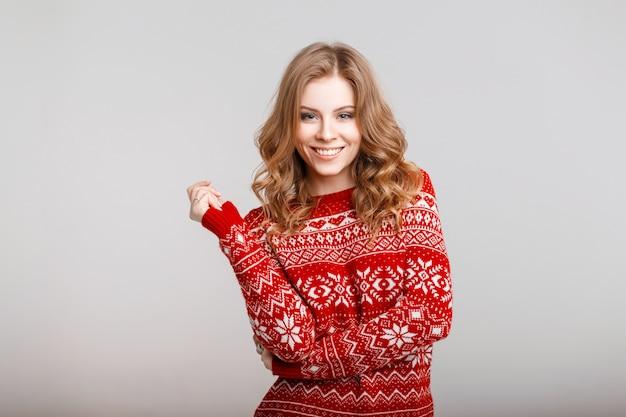 Ragazza felice con un sorriso in un maglione vintage rosso invernale su sfondo grigio