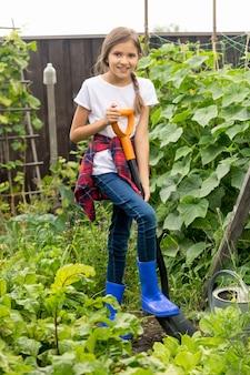 Ragazza felice che lavora al giardino con la pala sho