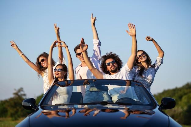 Felici ragazze e ragazzi con gli occhiali da sole sono seduti in una cabriolet nera sulla strada alzando le mani e sorridendo in una giornata di sole. .