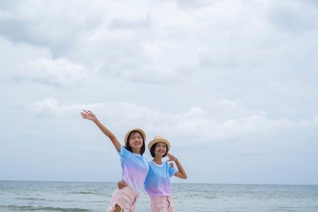 Ragazze giovani felici indossano cappelli e jeans rosa in spiaggia con cielo nuvoloso