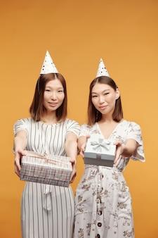 Felice giovani bellissime femmine asiatiche in abiti eleganti che ti guardano mentre passano scatole avvolte e imballate con regali di compleanno