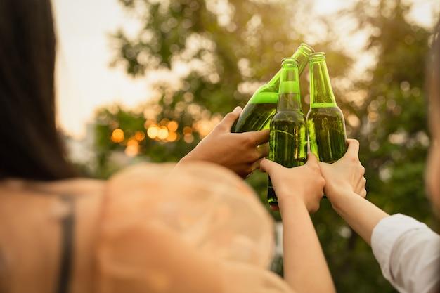 Felice giovane gruppo di amici, feste e bevande.