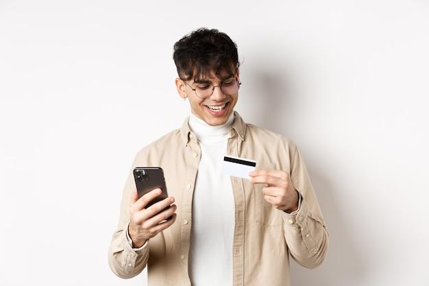Felice giovane ragazzo in bicchieri che fanno acquisti online, guardando la carta di credito in plastica e tenendo lo smartphone, in piedi sul muro bianco.