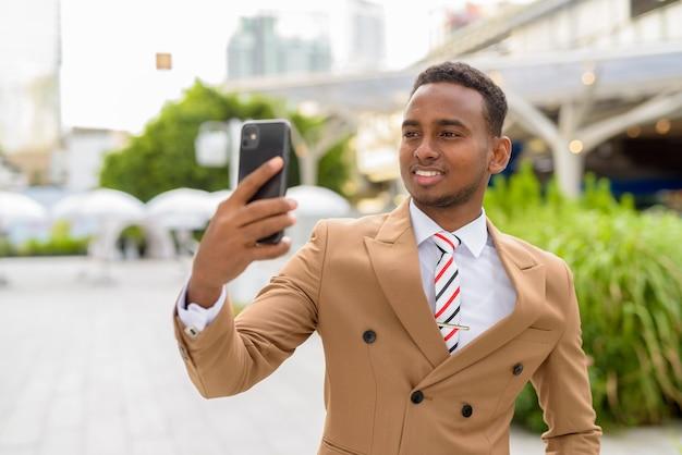 Felice giovane uomo d'affari africano bello prendendo selfie in città