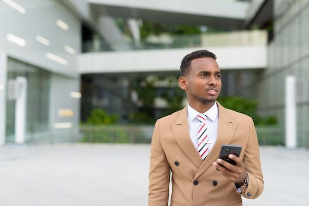 Felice giovane uomo d'affari africano bello pensare durante l'utilizzo del telefono in città