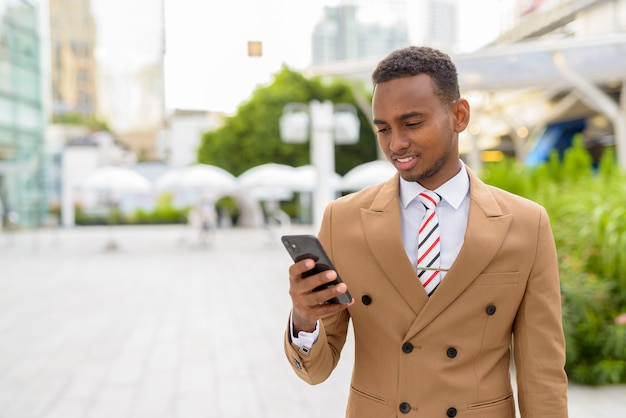 Felice giovane uomo d'affari africano bello utilizzando il telefono in città all'aperto