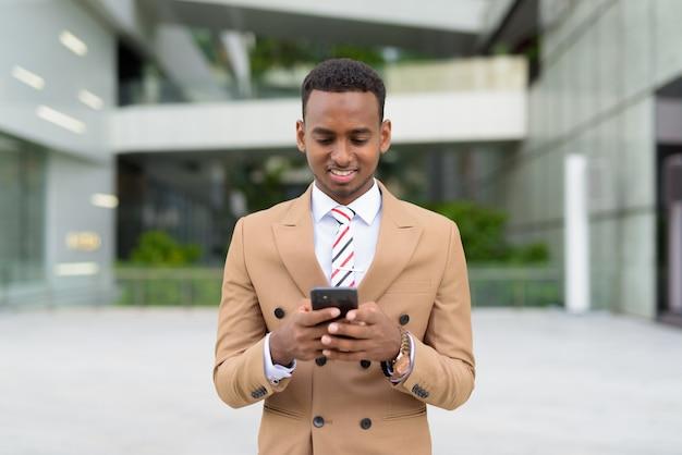 Felice giovane uomo d'affari africano bello utilizzando il telefono in città