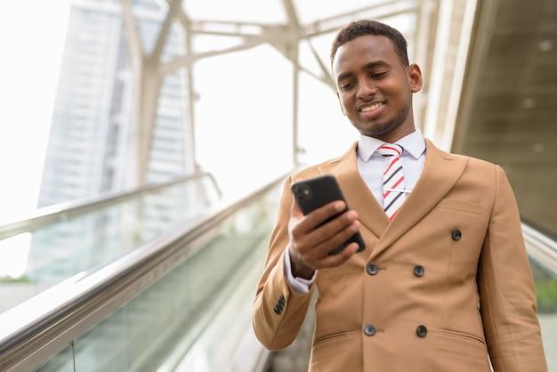 Felice giovane uomo d'affari africano bello utilizzando il telefono mentre si sposta lungo la scala mobile in città