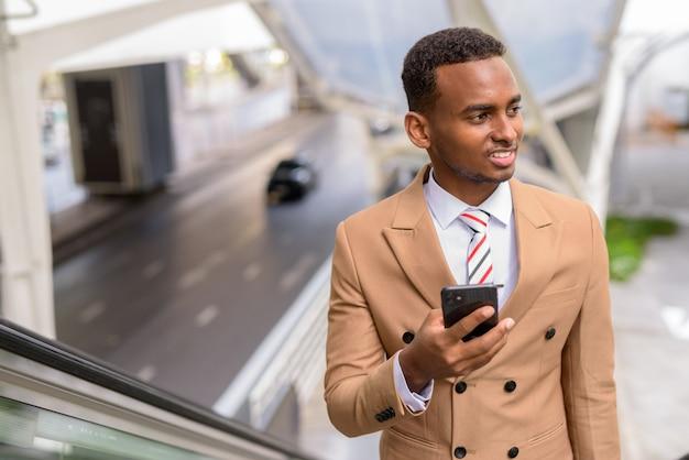 Felice giovane uomo d'affari africano bello utilizzando il telefono mentre si sposta la scala mobile in città