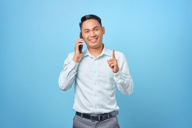 Felice giovane uomo d'affari bello che parla al telefono cellulare e punta il dito con un'idea