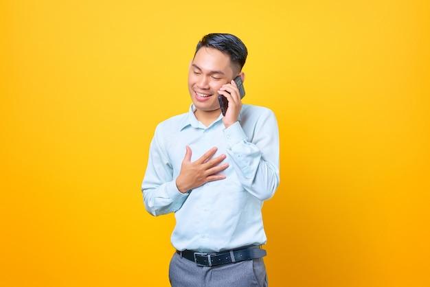 Felice giovane uomo d'affari bello che parla su smartphone e tiene altri palmi su un petto