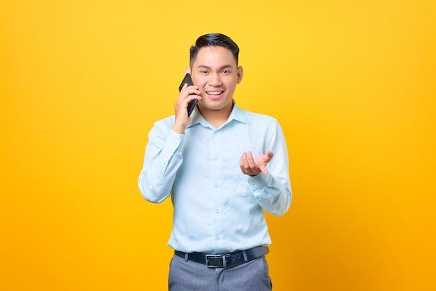 Felice giovane uomo d'affari bello che parla su smartphone e mano alzata su sfondo giallo