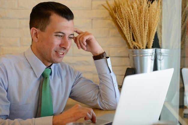 Felice giovane uomo d'affari bello utilizzando laptop presso la caffetteria