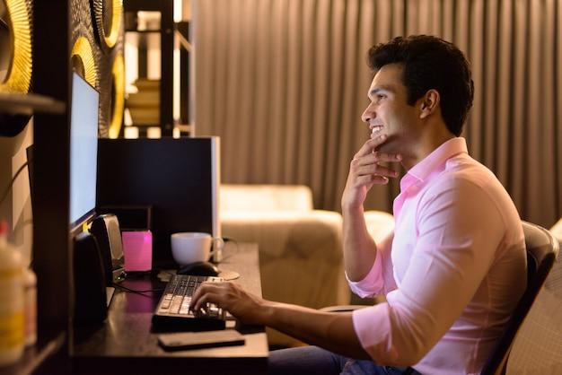 Felice giovane uomo d'affari indiano bello pensare mentre si fa gli straordinari a casa