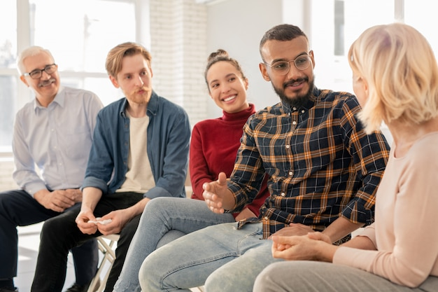 Felice giovane uomo bello in abbigliamento casual a parlare con uno dei compagni di gruppo o un consulente alla sessione psicologica