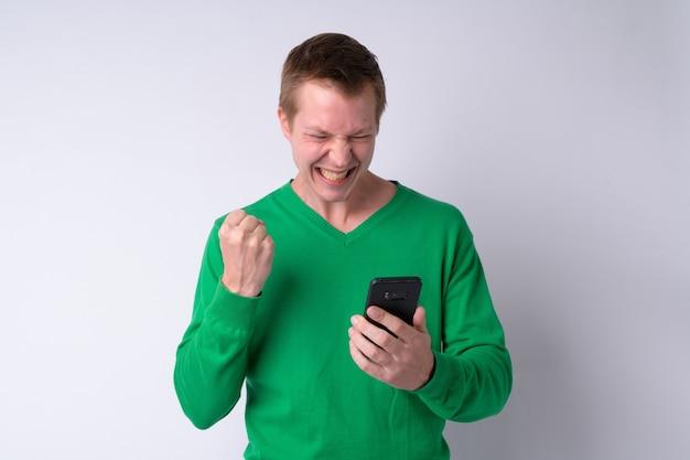 Felice giovane uomo bello utilizzando il telefono e ottenendo buone notizie