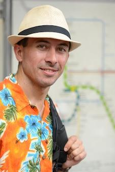 Felice giovane turista bello con lo zaino alla mappa del percorso nella stazione ferroviaria