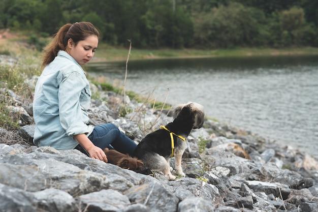 Giovane donna felice dei pantaloni a vita bassa asain con i suoi cani divertenti che si siedono sulla roccia accanto al bacino idrico.