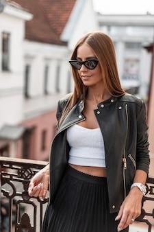 Felice giovane donna hipster con un bel sorriso in occhiali da sole alla moda in una giacca nera in una gonna in un top bianco alla moda gode di relax in piedi su un balcone vintage. ragazza allegra all'aperto.