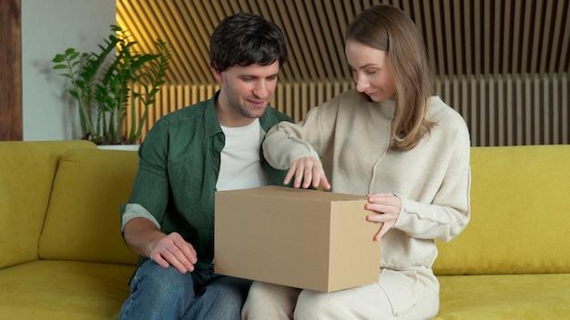 I giovani clienti felici della moglie e del marito aprono la scatola della spesa che compera in linea mentre si siede a casa sul sofà giallo