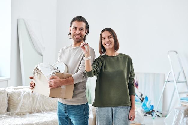 Felice giovane marito e moglie con sorrisi a trentadue denti in piedi davanti alla telecamera mentre femmina che mostra la chiave dalla nuova casa o appartamento