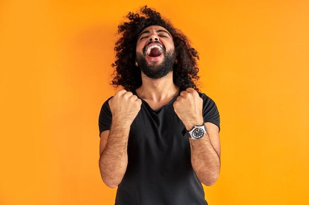 Felice giovane uomo indiano o arabo che celebra sorpreso