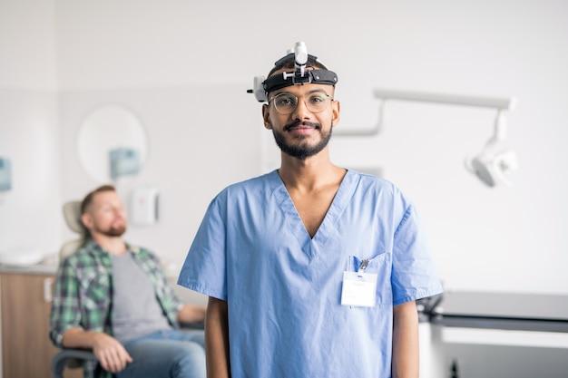 Felice giovane medico interculturale in uniforme e attrezzature mediche sulla testa in piedi davanti alla telecamera