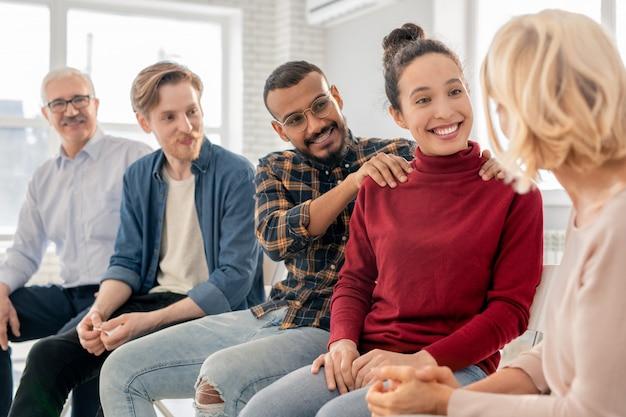 Felice giovane coppia interculturale in abbigliamento casual guardando bionda donna matura mentre si parla con lei alla sessione