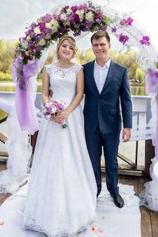 Felice giovane coppia appena sposata in piedi sotto i cancelli floreali alla cerimonia di nozze