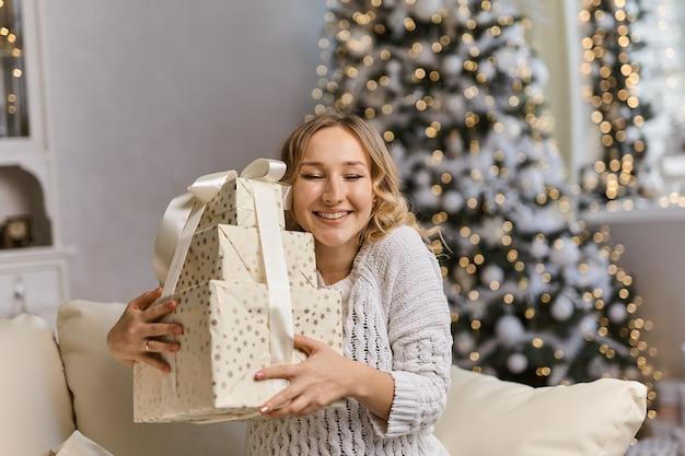 Felice giovane donna che tiene e abbraccia la confezione regalo