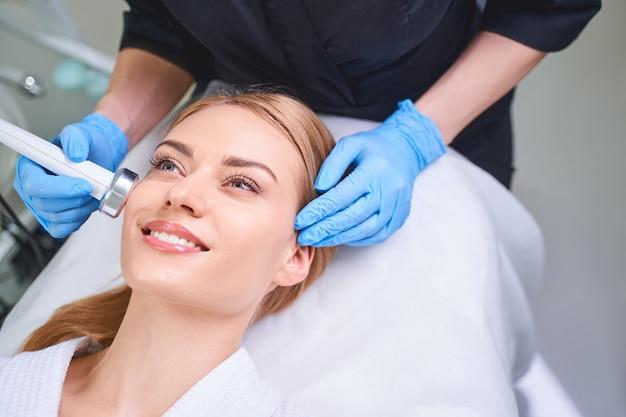 La giovane donna felice si sta prendendo cura del suo viso ricevendo un trattamento ad ultrasuoni da un professionista