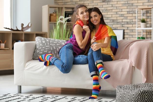 Felice giovane coppia lesbica con bandiera arcobaleno a casa
