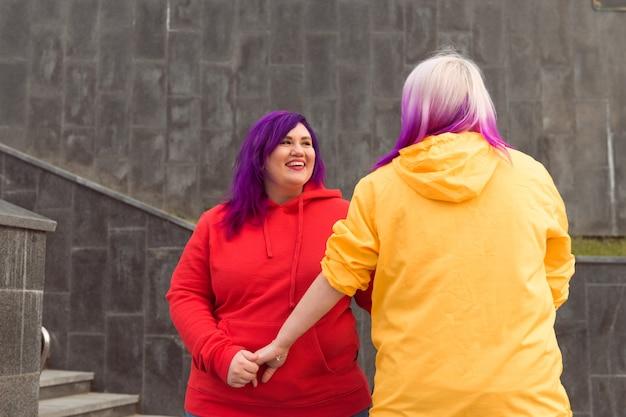 Felici giovani lesbiche vestiti di colore rosso e giallo che si abbracciano tenendosi per mano all'aperto